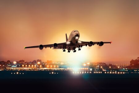 Passenger plane takes off at dusk, with the lights of the airport in the background Stock fotó