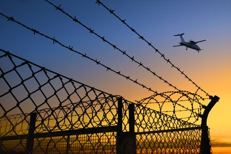 Airplane takes off at dusk, with fences and barbed wire wire in the foreground