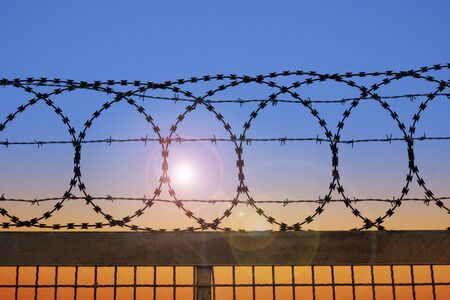 Behind a barbed wire fence, the sun goes down