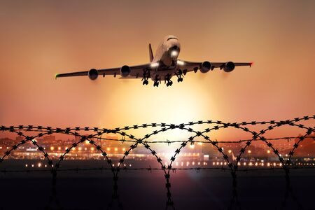 Passenger plane takes off at dusk, in the background the lights of the airport can be seen and in the foreground a barbed wire fence Stock fotó