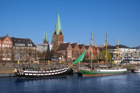 Sailing ships lie on the banks of the river Weser in the Hanseatic city of Bremen with blue sky Stock fotó