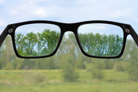 Black glasses in front of green landscape, sharpness can only be seen in the lenses Archivio Fotografico - 130136232