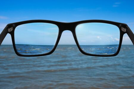 Black glasses in front of leaden sea, sharpness can be seen only in the lenses