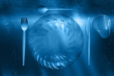 Plastic utensils and plastic cutlery float in the depths of the sea