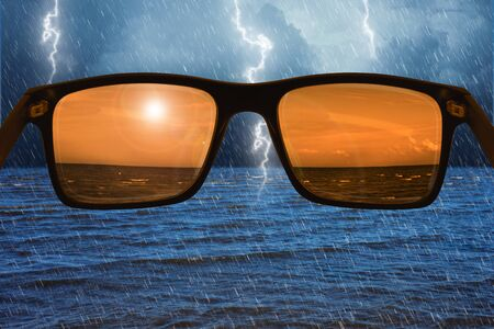 Looking through glasses, the storm appears like a calm sunny day Archivio Fotografico - 130136236