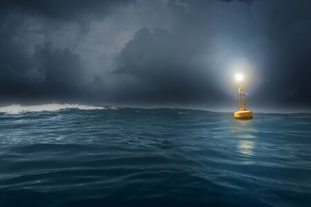 A yellow buoy drifts in the rough sea at dusk