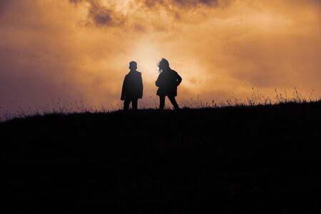 Two children are standing on a hill behind which the sun goes down Imagens