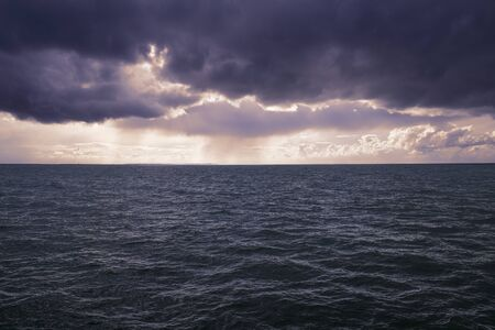 Purple clouds float dramatically over the open sea Stockfoto