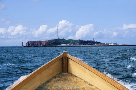 View from the sea from a wooden boat to the rocky island Helgoland in good weather Foto de archivo
