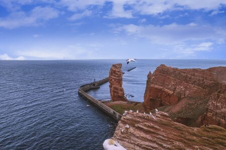 The long Anna and the red rock landscape of Helgoland with blue sky