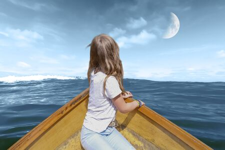 A girl drives in a boat made of wood in waves over the sea, in the sky is the half moon to see Zdjęcie Seryjne
