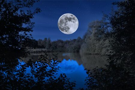 The full moon is reflected in a starry night in a lake Фото со стока