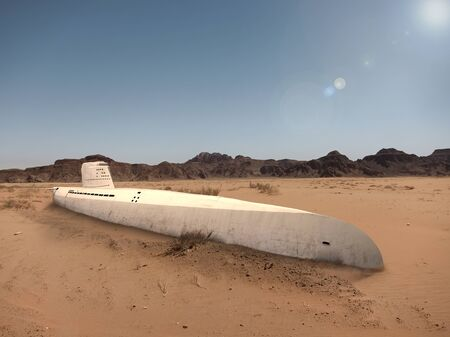 An old submarine is stuck in the sand of the desert Stock fotó