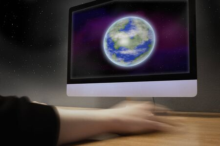 A hand moves the computer mouse, the earth can be seen on the monitor
