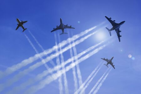Airplanes fly against a blue sky, leaving contrails Standard-Bild