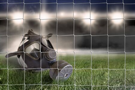 A soccer ball with a gas mask lies in the goal on the soccer field Banque d'images - 144071039