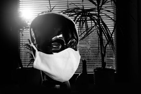 A black head is wearing a face mask, in the background is a window with a blind