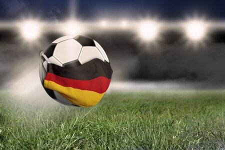 A soccer ball wears a face mask in the colors of the German flag