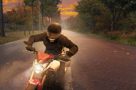 A motorcycle drives along a country road at dusk