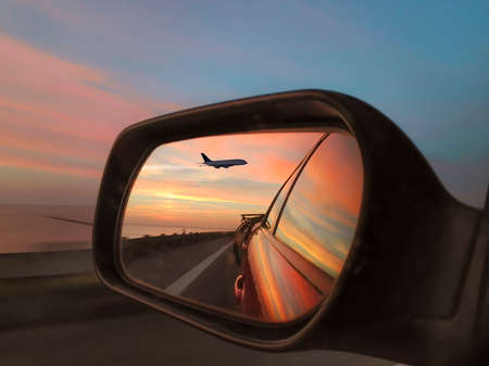 The evening sky and a passenger plane are reflected in the side mirror of a car