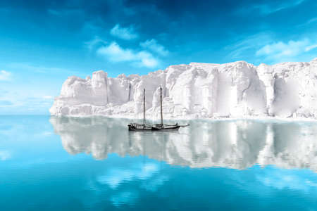 A sailing ship lies in front of an iceberg in the Arctic Sea Stock Photo