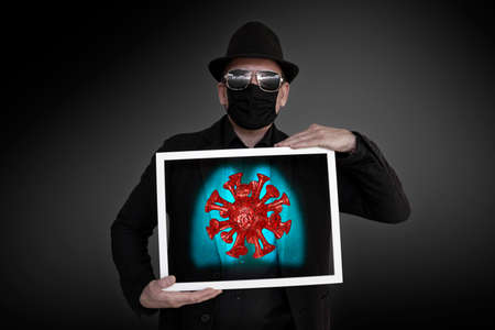 A man holds a picture frame in front of his chest, behind which a virus can be seen