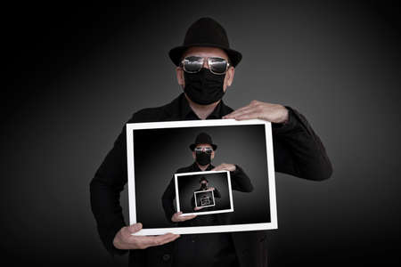 A man holds a picture frame in front of his chest in which he can be seen Stock Photo