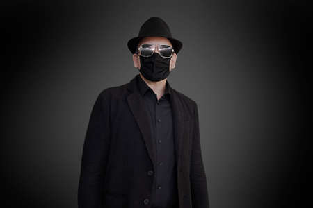 A fashion-conscious man in a black suit, face mask, hat and sunglasses
