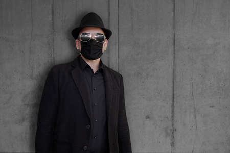 A fashion-conscious man wearing a black suit, face mask and hat stands in front of a concrete wall