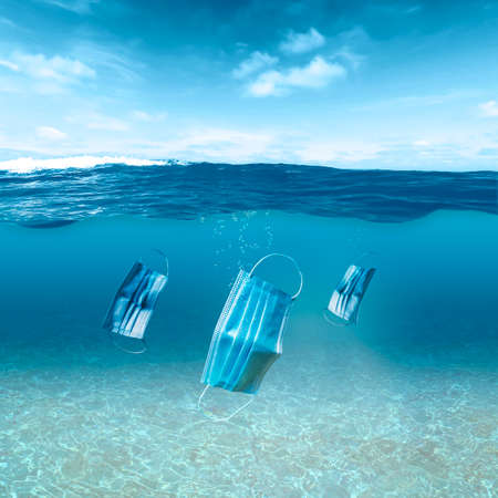 Three face masks float under the water surface in the ocean