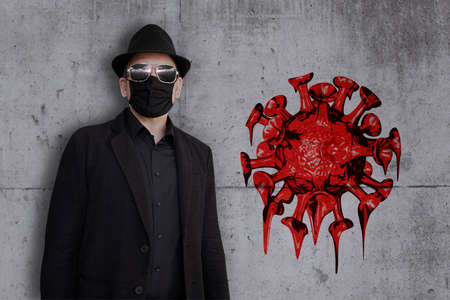 A man in a black suit stands in front of a concrete wall on which graffiti of a virus can be seen