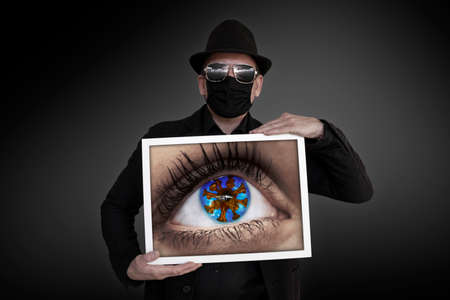 A man carries a picture frame in which one eye can be seen Stock Photo