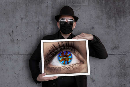 A man carries a picture frame in which one eye can be seen Archivio Fotografico