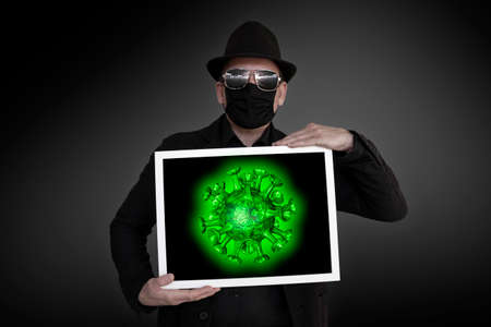 A man carries a picture frame in which a green virus can be seen