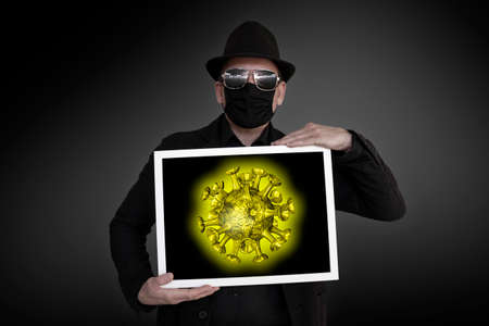 A man carries a picture frame with a yellow virus in it