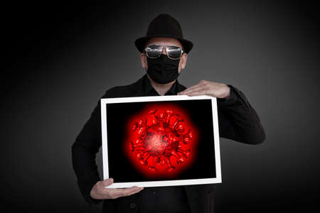 A man carries a picture frame in which a red virus can be seen