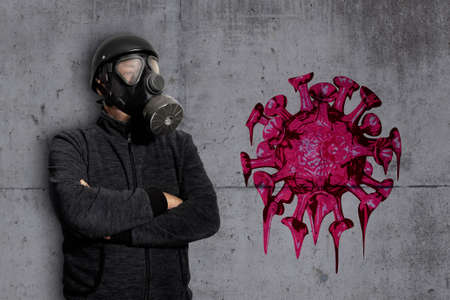 A man with a gas mask stands in front of a concrete wall on which graffiti can be seen Archivio Fotografico