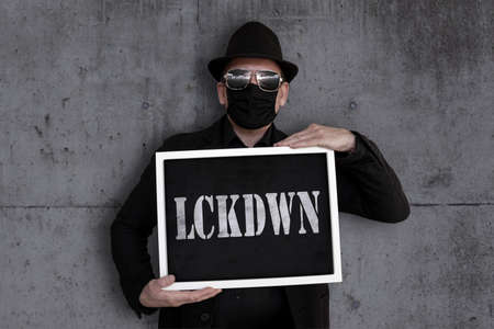 A man carries a blackboard with the word Lockdown written on it