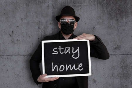 A man carries a blackboard with the word stayhome written on it