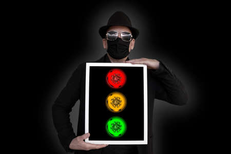 A man holds a picture frame in front of his chest in which a traffic light can be seen