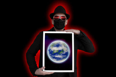 A man with a face mask holds a picture frame in front of his chest in which the earth can be seen Archivio Fotografico