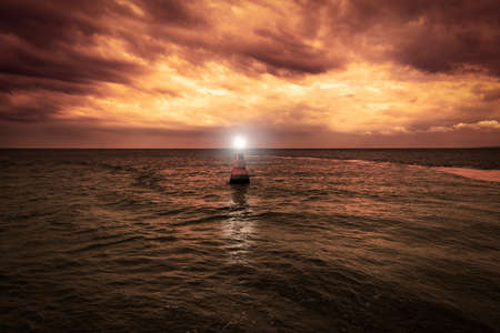A yellow buoy drifts in the sea at dusk