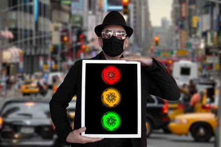 A man stands on a street and holds a picture in which a traffic light can be seen Archivio Fotografico