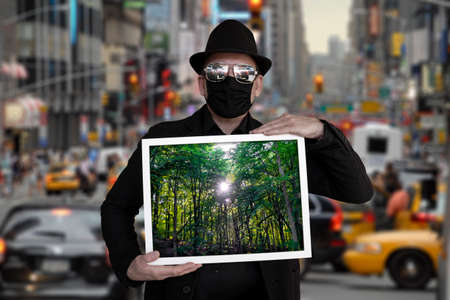 A man is standing on a road and holding a picture in which a forest can be seen