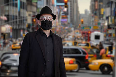 A fashion-conscious man wearing a black suit, face mask, hat and sunglasses stands in front of a busy street