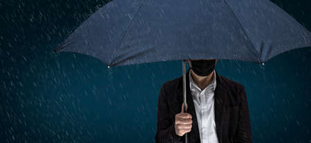 A man with a face mask is standing with an umbrella in the rain Archivio Fotografico