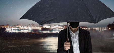 A man with a face mask stands with an umbrella in front of the lights of a city