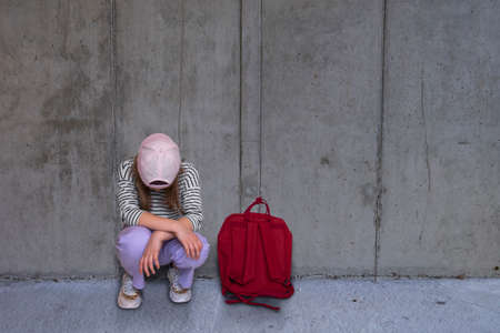 A girl crouches with her head bowed in front of a concrete wall