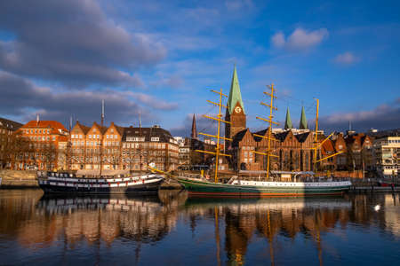 Ships lie on the promenade on the Weser in Bremen and are reflected in the water