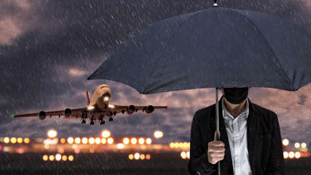 A man with a face mask and an umbrella at the airport